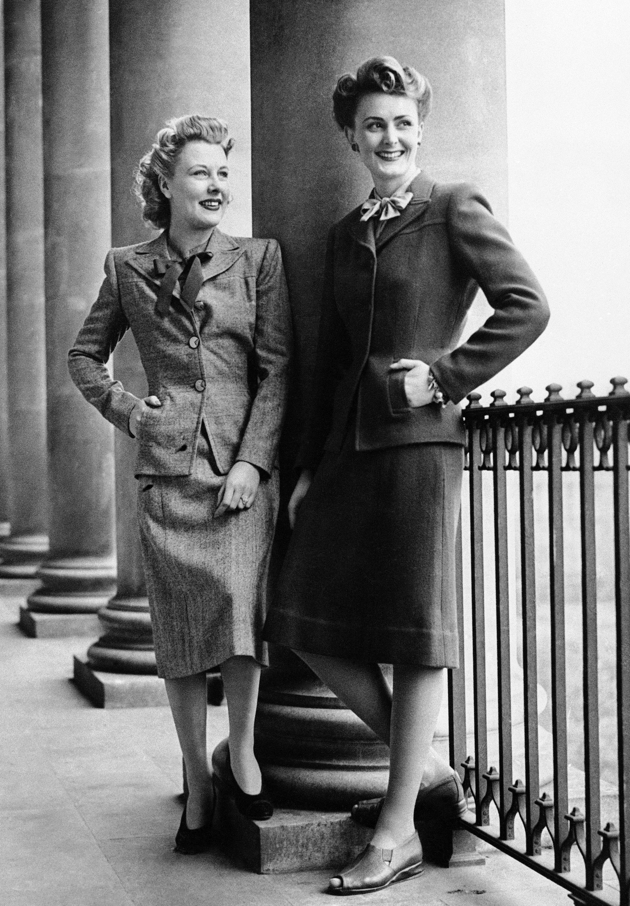 Britain's fashion experts submit their designs to the Board of Trade, which advises changes to facilitate mass production of the clothes. In photo at left: an original costume, left, as submitted by designers, and the approved utility garment, right, which shows little difference between the two suits. At right: the original, left, compared with the smart utility counterpart, right, which was approved by the board at a fashion show in London.