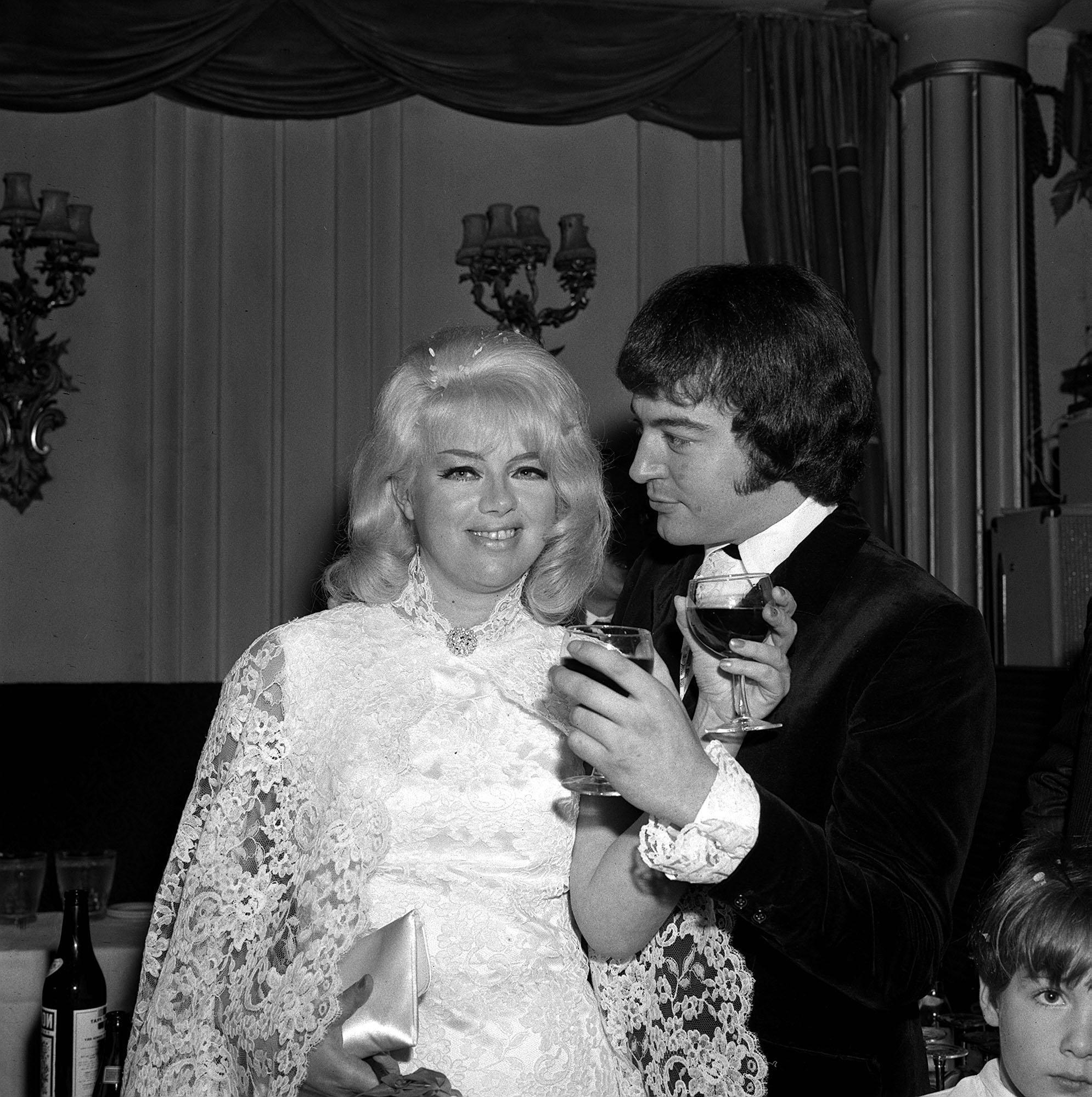 Diana Dors and her bridegroom Alan Lake exchange toasts at the reception at the Astor Club, after their wedding at Caxton Hall on 23 November 1968. They remained married until Dors' death in 1984.