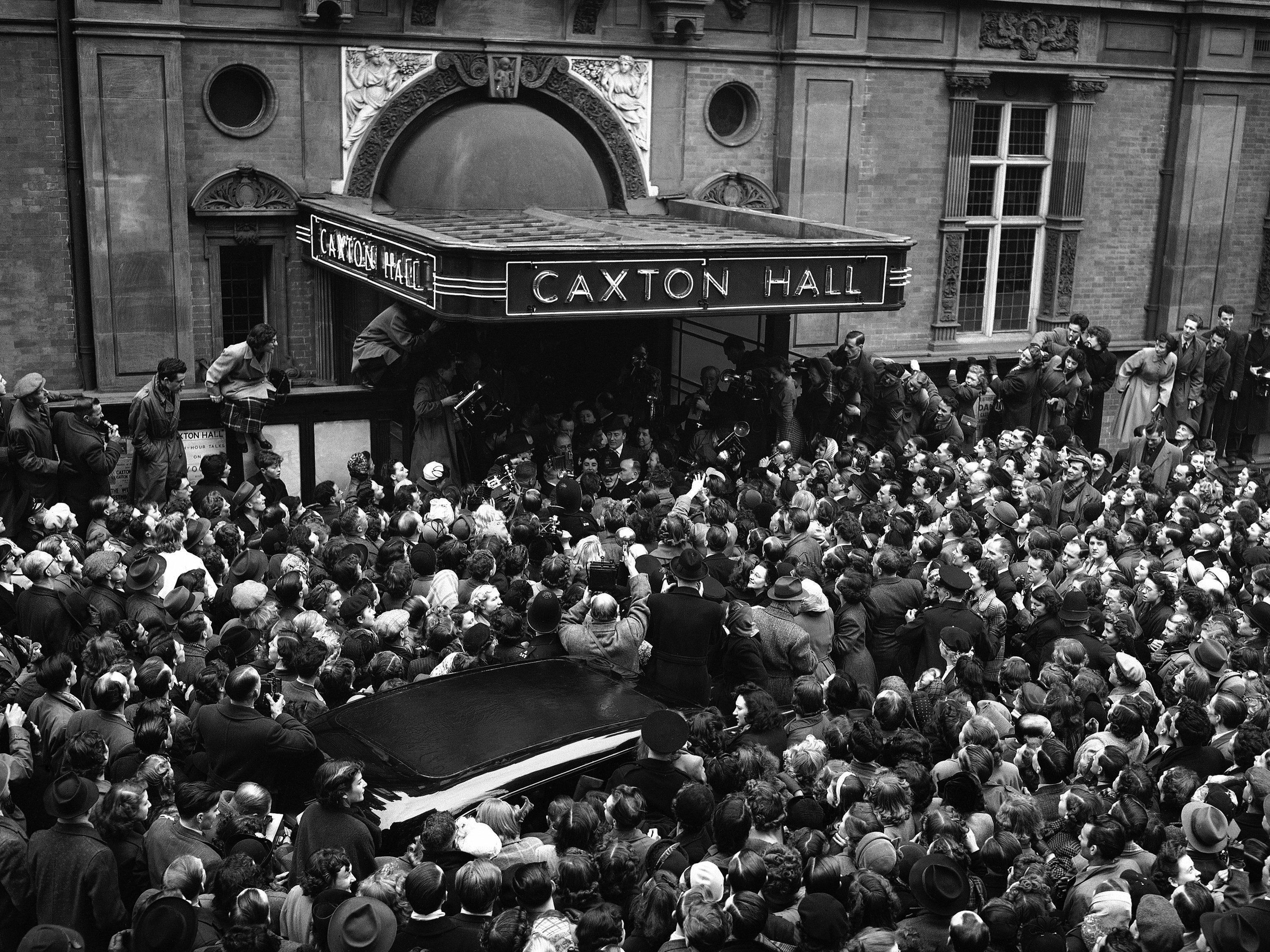 British screen star Elizabeth Taylor and her husband, English actor Michael Wilding stand at the door of London's Caxton Hall, United Kingdom before the huge crowd which massed to greet them after their wedding on the morning of Feb. 21, 1952. (AP Photo)