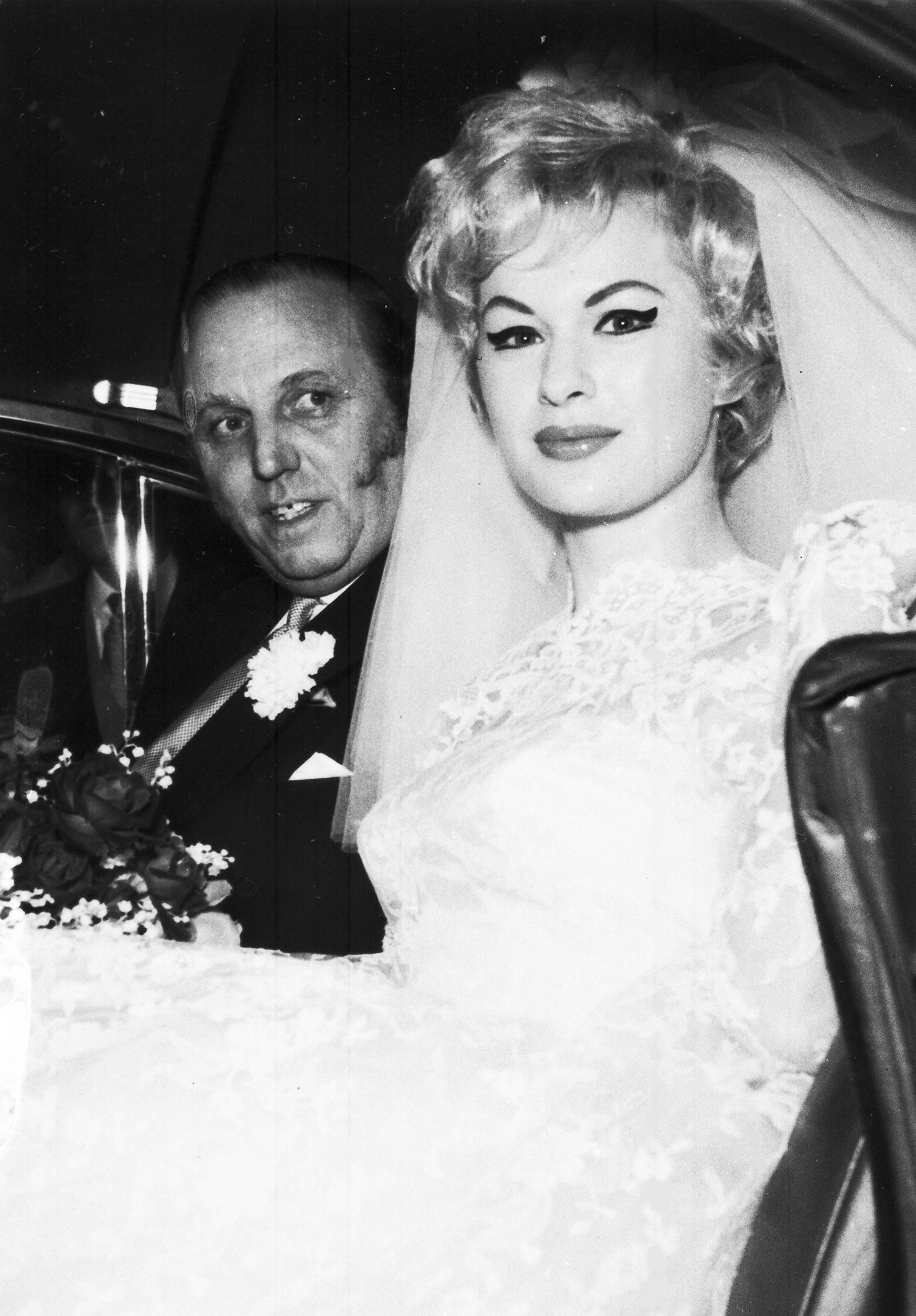 "Antique dealer and night club owner Horace Dibben, 54, with his bride former Mariella Novotny, an 18-year-old night club dancer, after their wedding at Caxton hall, London, Jan. 29, 1960. Christine Keeler later recalled: ""She had a tiny waist that exaggerated her ample figure. She was a siren, a sexual athlete of Olympian proportions - she could do it all. I know. I saw her in action. She knew all the strange pleasures that were wanted and could deliver them."" (AP Photo)"