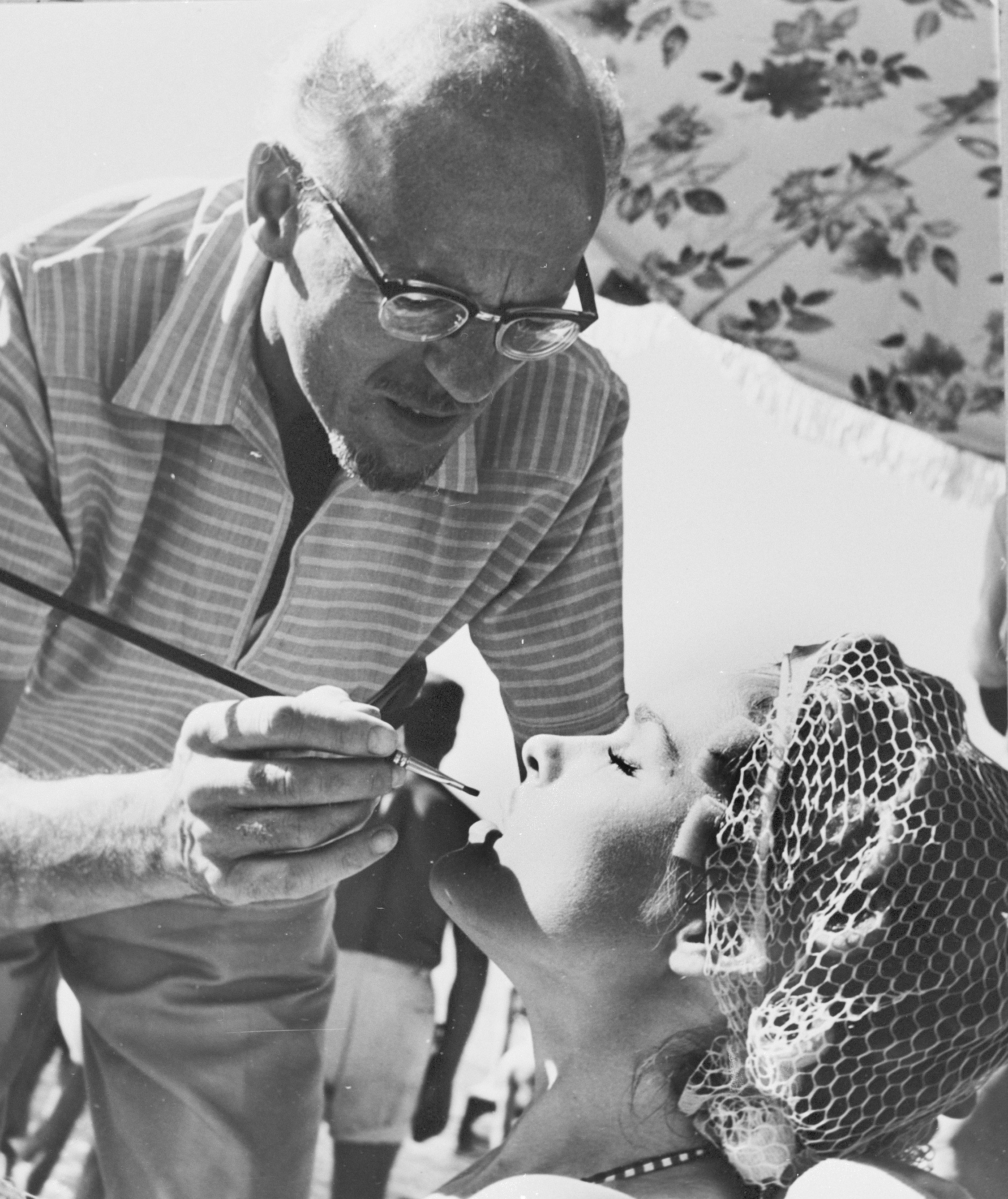 """Movie makeup man John O'Gorman uses a lipstick brush in preparing actress Ursula Andress for her starring role in """"Dr. No"""", on location in Jamaica, British West Indies, May 17, 1962. The heat and tropical atmosphere of Jamaica caused quite a problem for John O'Gorman and his staff. the make-up started to run so quickly that he had to on guard every moment to touch up the principals between shots. (AP Photo)"""