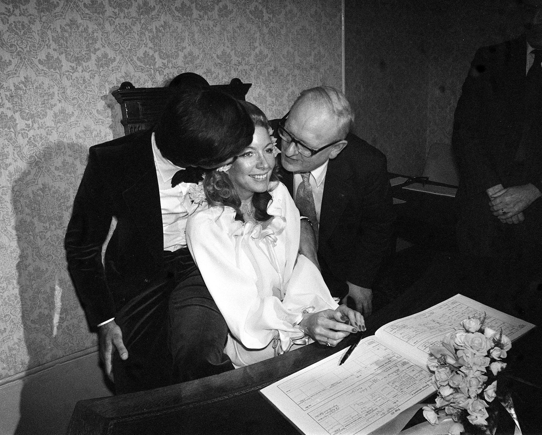 30/12/1977: Mr Robert Claiborne-Dixon and the former Miss Regina Dangerfield after they became the last couple to wed at Caxton Hall, Westminster register office, which is closing after 44 years of cheers, rice, confetti and romance. The man kissing the bride is Superintendent Registrar Mr Donald Boreham, who wed them.