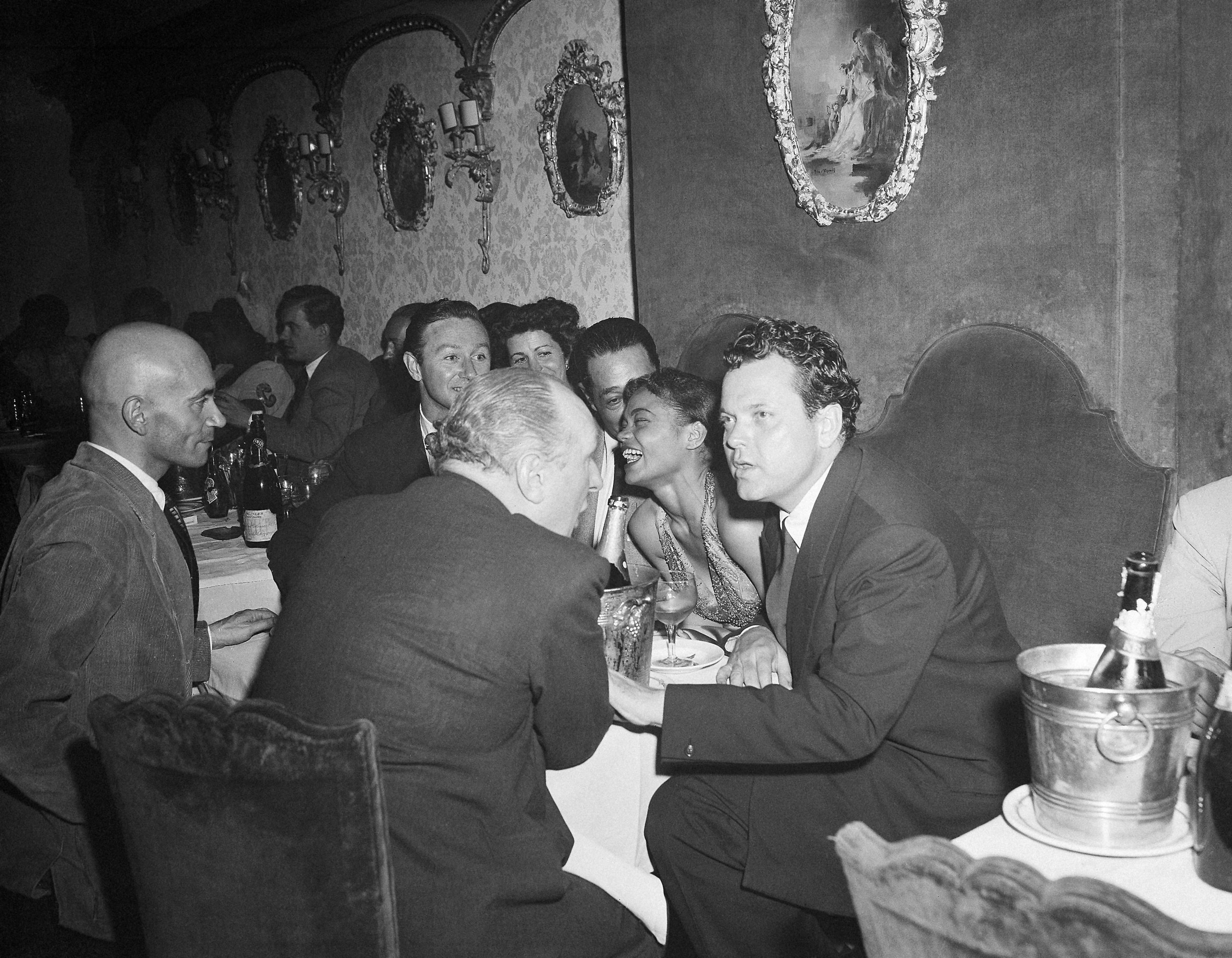 "After the opening of his play ""The Blessed and the Damned"" at the Theatre Edouard VII in Paris on June 20, 1950, author, producer and leading man Orson Welles went out to celebrate in a Montmartre nightclub. He is talking with Hilton Edwards, who is also in the play. Between them is leading woman Eartha Kitt. (AP Photo/Jean Aubry)"