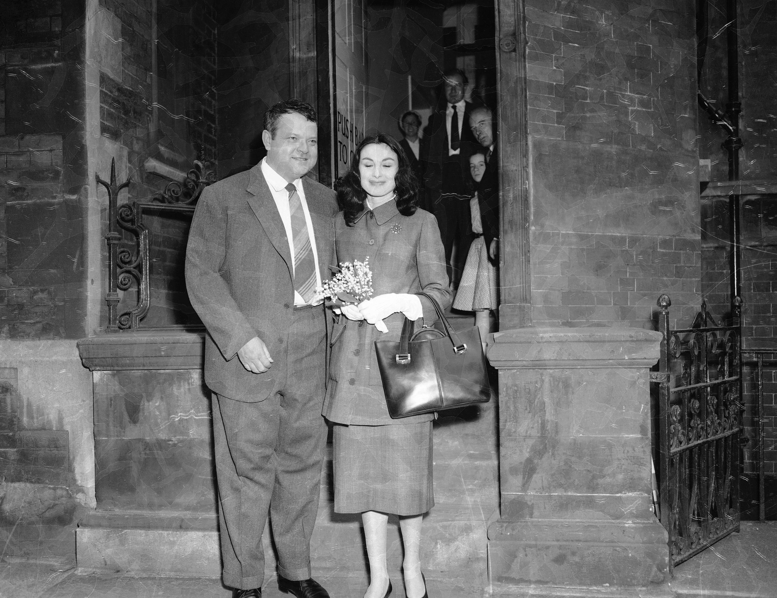Orson Welles, former husband of Rita Hayworth, smiles happily as he poses with his Italian actress bride Paoula Mori, 24, outside London's Caxton Hall register office after their marriages, May 8, 1955. They first met in Rome three years ago. Welles proposed in Spain. The bride is an Italian countess. She does not use her title. (AP Photo)