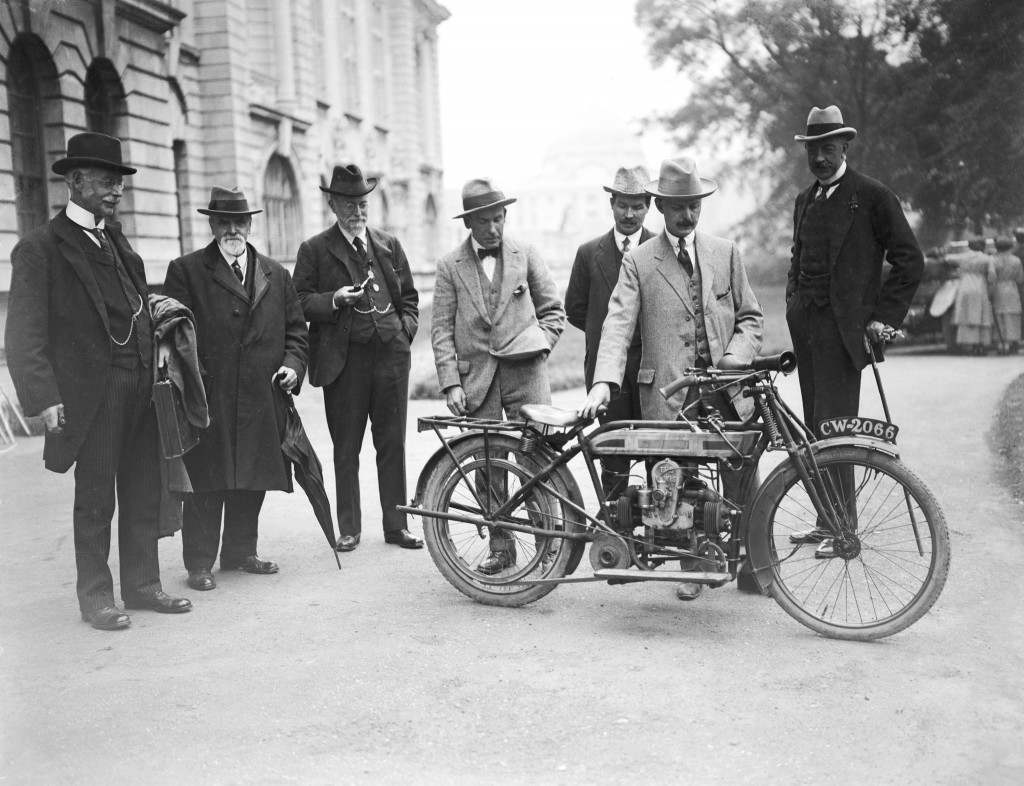 English engineer, Sir Charles Parsons (left) surveys his new invention, a new motorcycle engine, as members of the British Association of Scientists take a keen interest. Thomas Edgar Lewis is seen holding the machine Ref #: PA.11397157  Date: 26/08/1920
