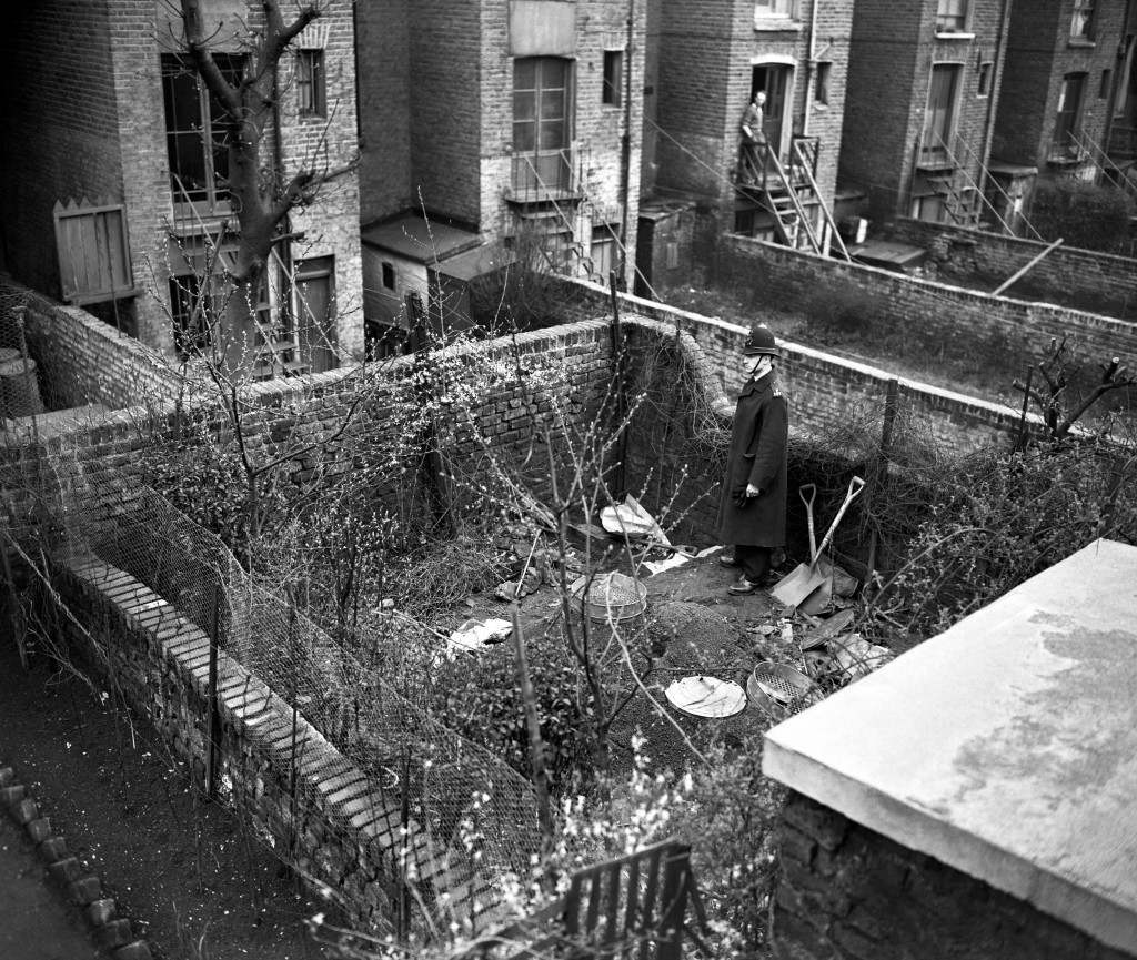 A policeman in the garden of 10 Rillington Place in Notting Hill, London, where police found human bones buried a few inches under the soil. They had been burned in an attempt to destroy them. The bodies of four strangled women have already been discovered at the address. Police are searching nationwide for suspect John Reginald Christie. Ref #: PA.1161421  Date: 28/03/1953