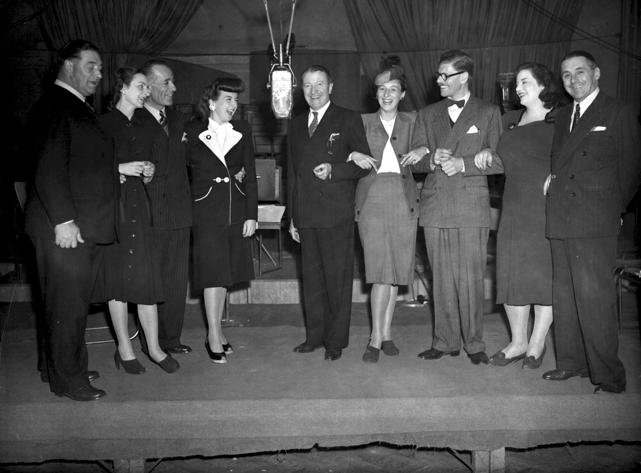 "From left to right: Fred Yule, Joan Harben, Hugh Morton, Lind Joyce, Tommy Handley, Diana Morrison, Derek Gyler, Hattie Jackes and Jack Train during rehearsals for the radio show ""ITMA"" in London 25/09/1947"