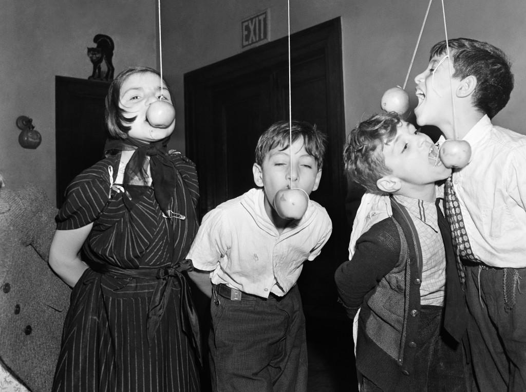 One of the games played at every Halloween party is eating, or rather, trying to eat apple suspended on a string with your hand behind you. They were few of the children of New York's Little Italy who were guests at the Annual Halloween Party sponsored by the Children's Aid Society in New York, Oct. 25, 1939.  Ref #: PA.12248517  Date: 25/10/1939