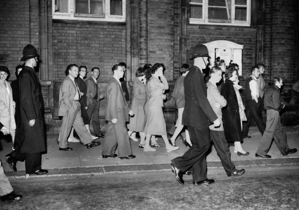Police walk along the edge of the pavement to ensure that the crowd keep moving at Notting Hill, in London, where more racial disturbances flared up. Ref #: PA.1330826  Date: 01/09/1958