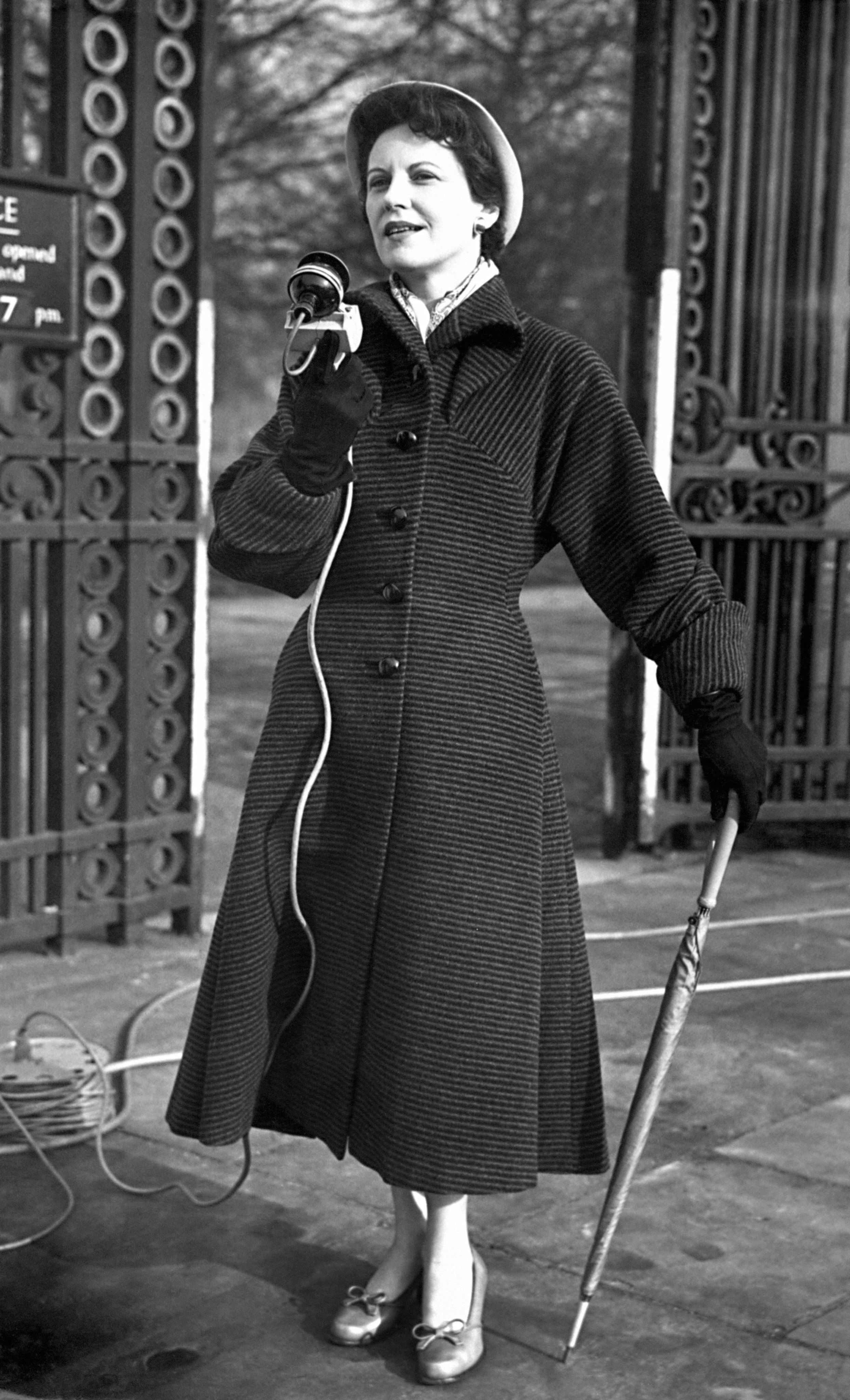 Microphone and umbrella in hand, Manchester born broadcaster Jessica Dunning makes an outside broadcast (from a position near Buckingham Palace) in an audition for commentators for the Coronation. It is thought women may be better able to handle some aspects of the day's ceremonies. 21/02/1953