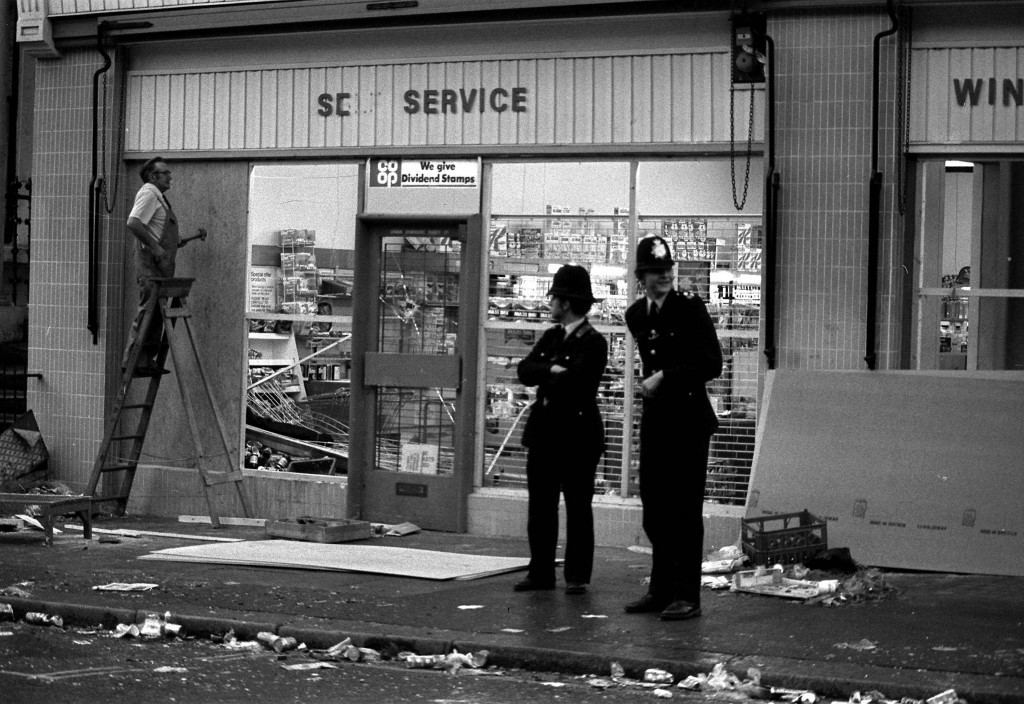 NOTTING HILL 1976: Police stand guard as a workman boards up the windows of the Co-op supermarket and off licence in Westbourne Park Road following last night's scenes of violence in Notting Hill, West London, when a West Indian carnival exploded into a riot. Ref #: PA.1416217  Date: 31/08/1976