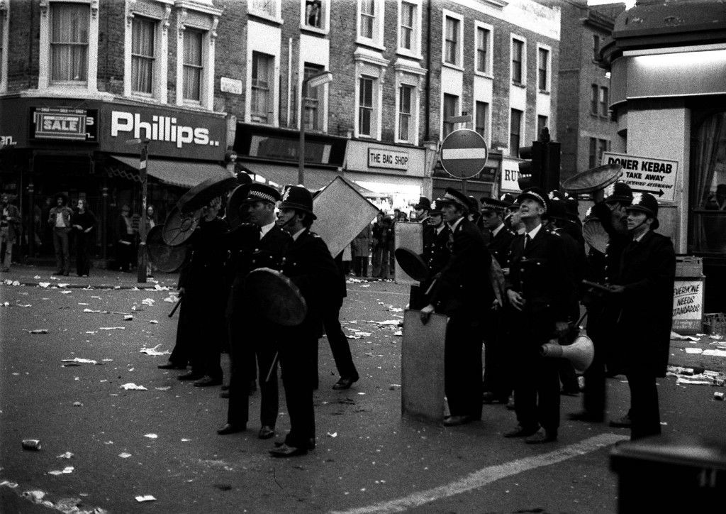 NOTTING HILL 1976: Police with drawn truncheons and using dustbin lids as shields in Notting Hill - a West Indian area of London - after the calypso carnival became a carnival of terror. Police fought running battles with people as rioters smashed shop windows and attacked fleeing Whites. Ref #: PA.1416370