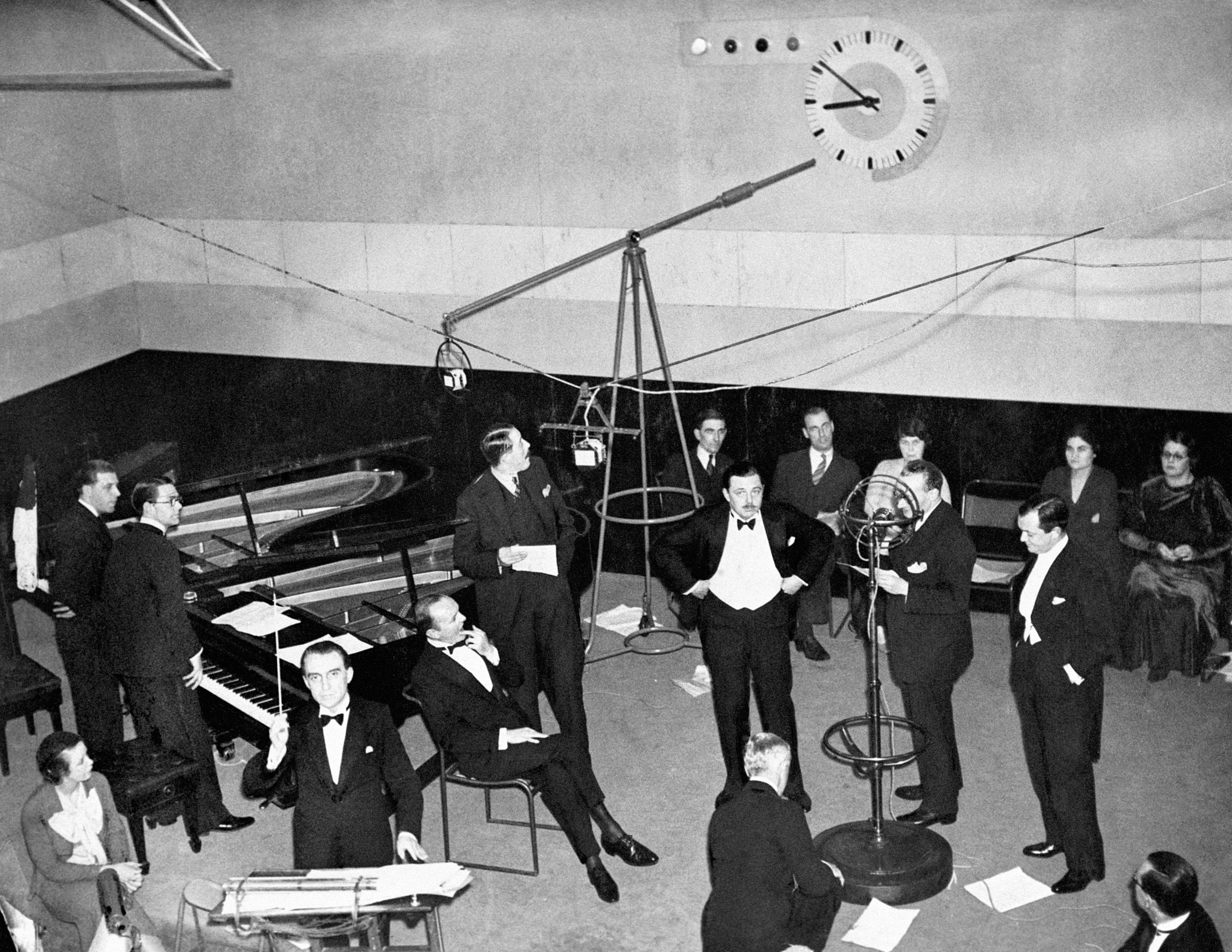 A scene in a 1930s BBC recording studio showing Christopher Stone, wearing a dinner jacket, bidding listeners 'Good Evening'. 01/07/1933