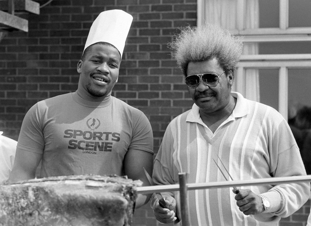 American World Heavyweight boxing champion Tim Witherspoon dons a chef's hat as promoter Don King prepares to carve the meat during an American-style barbecue hosted by the boxer in Basildon. Witherspoon defends his title against Frank Bruno at Wembley. Ref #: PA.1685295  Date: 13/07/1986