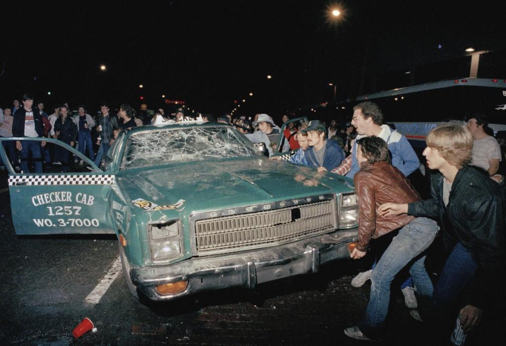 In this Oct. 14, 1984 file photo, a crowd attempts to topple a damaged taxi car outside Detroit's Tiger Stadium after the Detroit Tigers defeated the San Diego Padres to win the 1984 World Series baseball championship. (AP Photo) Ref #: PA.17098190  Date: 14/10/1984