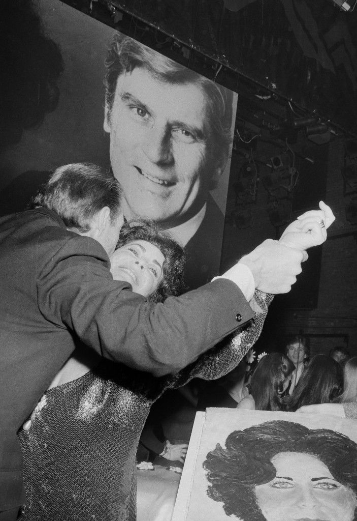 Designer Halston dances cheek-to-cheek with Liz Taylor at New York's Studio 54 March 7, 1978, as a cake bearing the actress's likeness sits in the foreground. Looming n background is a portrait of Taylor's husband John Warner. The occasion was a belated birthday party thrown by Halston to mark Liz's 46th birthday. (AP Photo) Ref #: PA.17590651 Date: 07/03/1978