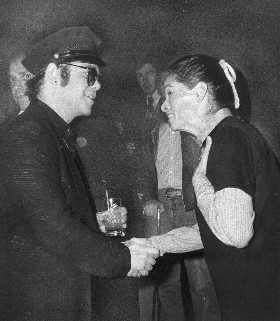 Rock star Elton John, in his trademark hat and tinted glasses, shakes hands with Geraldine Page at New York's Studio 54, Oct. 28, 1979. (AP Photo) Ref #: PA.17642634 Date: 28/10/1979