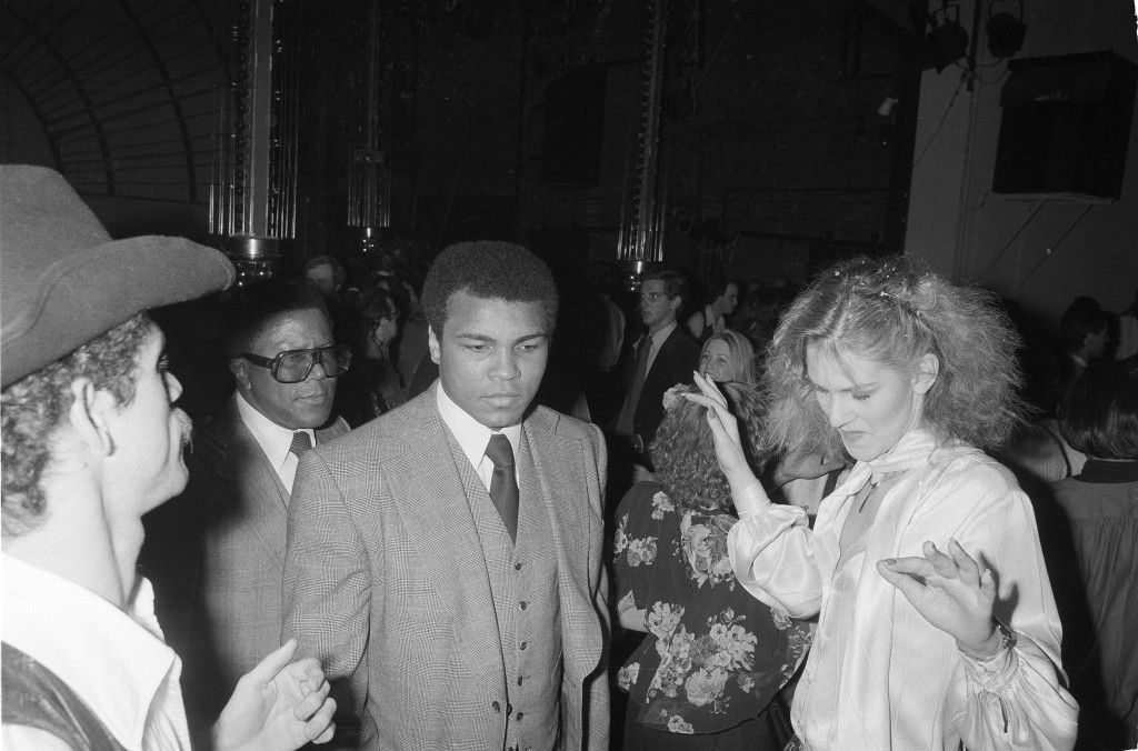 "Former heavyweight boxing champion Muhammad Ali maintains a neutral expression as he makes his way across the crowded dance floor of New York's popular disco, Studio 54, during a brief visit, March 25, 1978. Ali, remembered for his ""Ali Shuffle"" in the ring, did not dance during the visit. Others around him are unidentified. (AP Photo) Ref #: PA.17642642 Date: 25/03/1978"