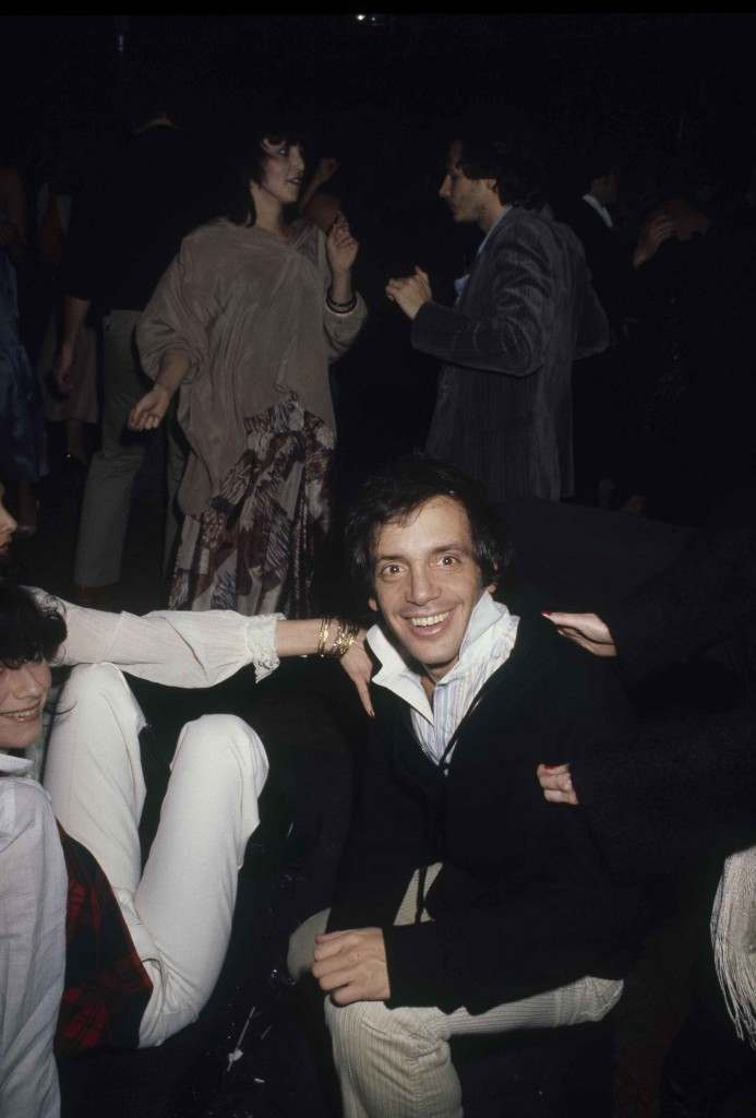 Studio 54 owner Steve Rubell smiles for a photographer inside his disco as revelers dance the night away in the background, in New York, Dec. 1977. (AP Photo) Ref #: PA.17645276 Date: 01/12/1977
