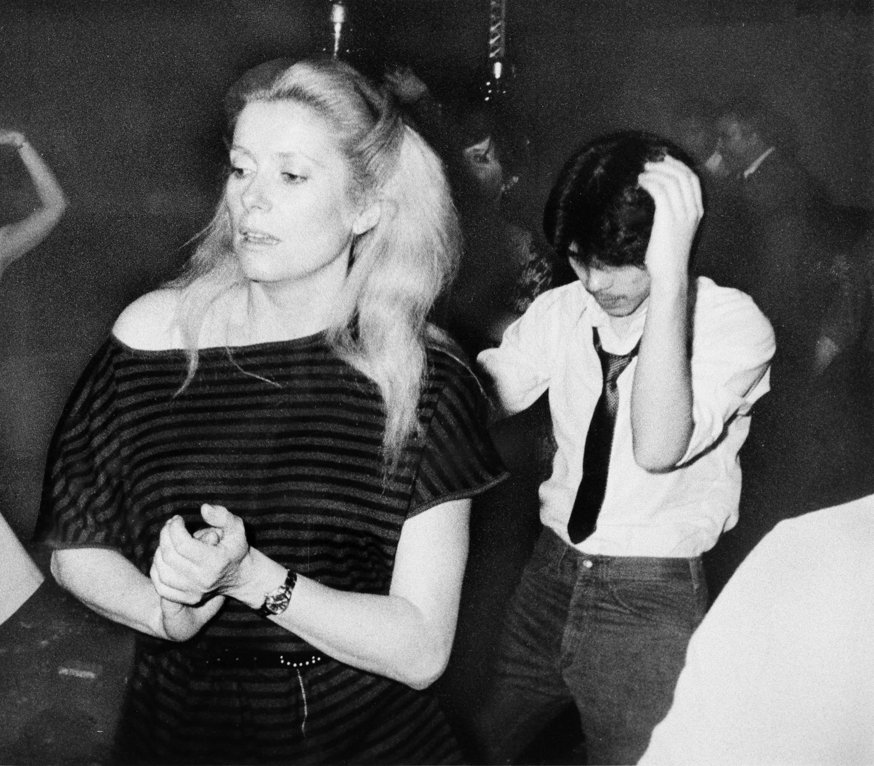 Actress Catherine Deneuve dances at New York disco, Studio 54, Feb. 27, 1979. Man at right is unidentified. (AP Photo)