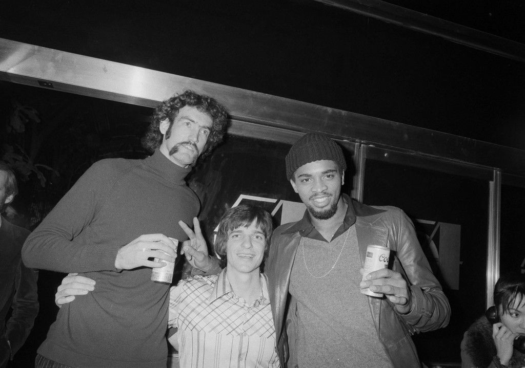 New Orleans Jazz basketball players, Pete Maravich, center, Rich Kelley, left, and Aaron James unwind at New York's Studio 54, Dec. 30, 1977, following an NBA game against the Knicks at Madison Square Garden. The Jazz players were in good spirits despite their team's 118-116 loss to the Knicks. (AP Photo)