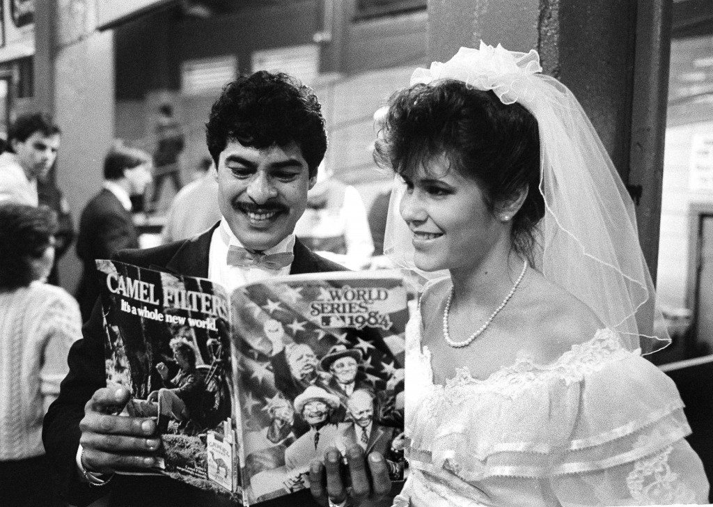 Anthony Sanchez and his bride of several hours, Charlotte, study a World Series program at Tiger Stadium in Detroit, Oct. 14, 1984. They came to game five of the Detroit-San Diego match-up from their wedding ceremony at nearby Dearborn Heights. The couple will live in Taylor, Mich., but not until after the baseball game. (AP Photo/Mark Duncan) Ref #: PA.18100716  Date: 14/10/1984