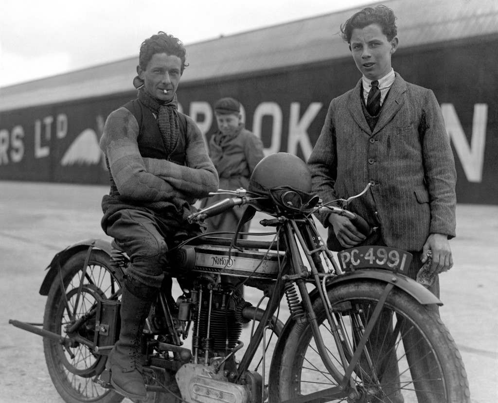 "Albert ""Bert"" Denly, Motorcyclist, practising at the Brooklands circuit on his Model 18 Norton. The boys in the image are unidentified Ref #: PA.5362154  Date: 06/04/1925"