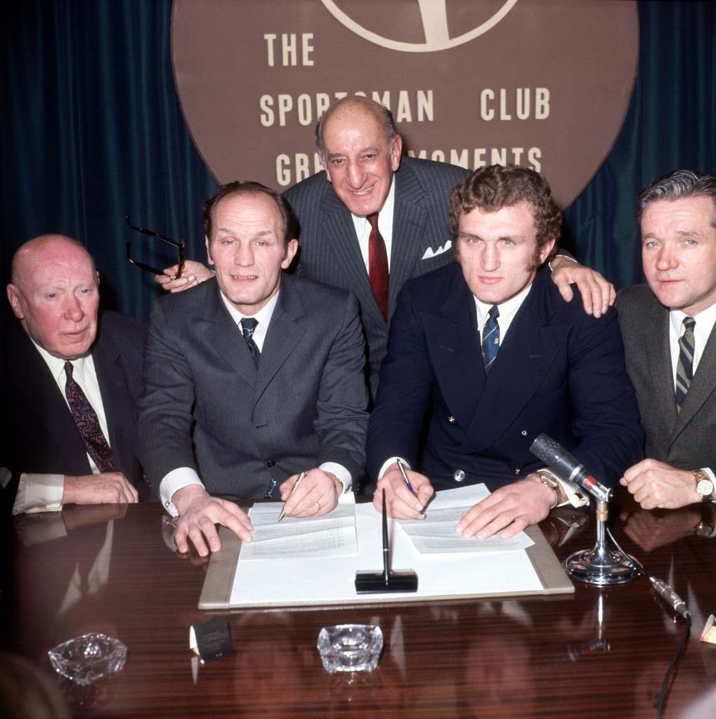 Boxing - British, Commonwealth and European Heavyweight Championship - Henry Cooper v Joe Bugner - Press Conference Joe Bugner (second r) and Henry Cooper (second l) sign contracts to meet each other in March 1971, watched by promoter Harry Levine (c), Cooper's manager Jim Wicks (l) and Bugner's manager Andy Smith (r) Ref #: PA.636296  Date: 27/01/1971