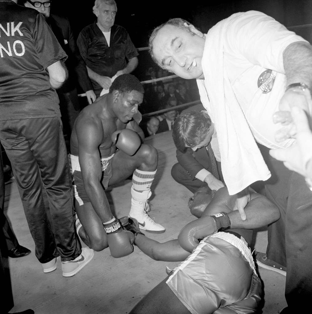 Boxing - Heavyweight Bout - Frank Bruno v Larry Frazier - Royal Albert Hall, Kensington, London Frank Bruno (l) and his cornerman Dennie Mancini (r) check on Larry Frazier (c) after the second round knockout that ended the fight Ref #: PA.751993  Date: 04/12/1985