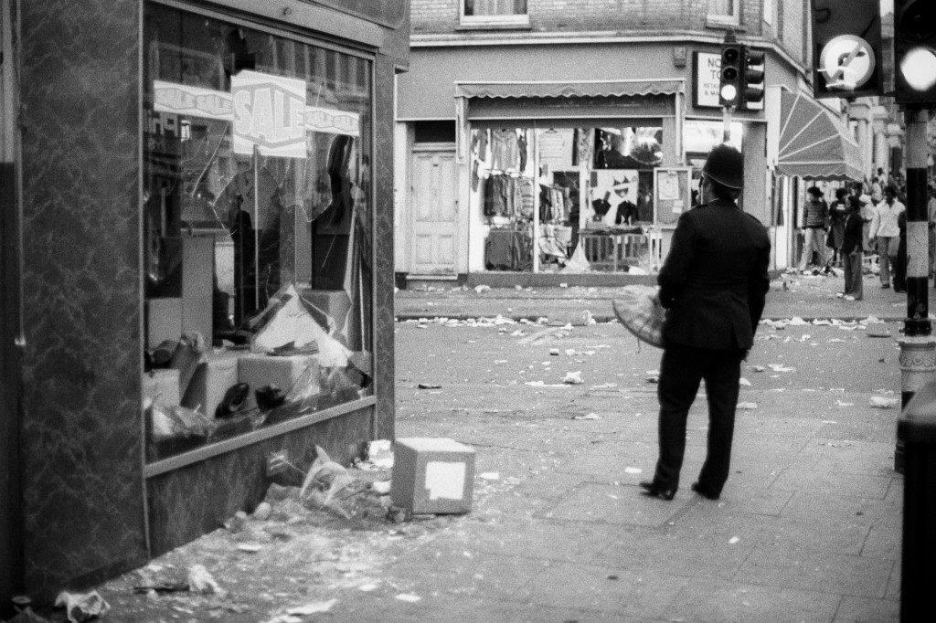 A policeman with a dustbin lid for a shield stands by a shattered shop window in Notting Hill - a predominantly West Indian area - tonight after a riot broke out during the mostly broken windows shop front peaceful Calypso Carnival. Police fought running battles with black youths as rioters went on an orgy of destruction. Ref #: PA.7694390  Date: 30/08/1976