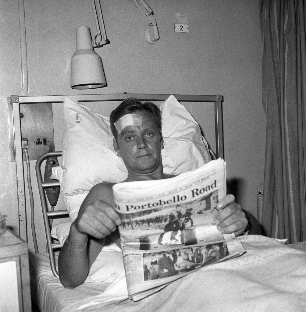 Reading an evening paper in bed at St Charles' Hospital, Ladbroke Grove, west London today, is Inspector Ian Quinn, part of a police reinforcement from Gerald Road police station, Pimlico, called in to deal with yesterdays race riots at Notting Hill. The inspector received a head wound and was among 325 policemen injured when the Notting Hill Carnival turned violent.  Ref #: PA.7694405  Date: 30/08/1976