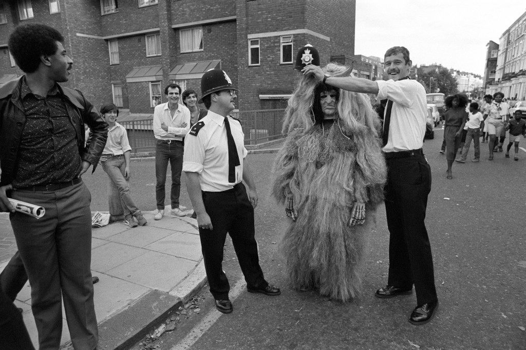 A Notting Hill Carnival witch doctor gets magical aid in the form of a policeman's helmet during peaceful festivities. Ref #: PA.7740092  Date: 29/08/1982