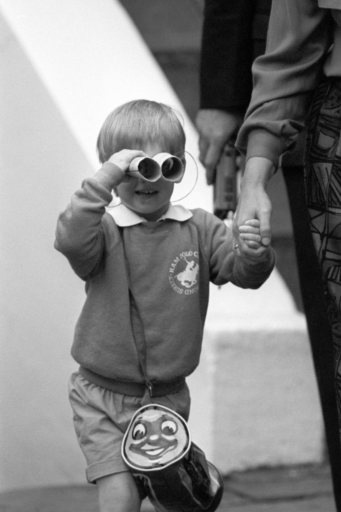 Prince Harry, three-year-old son of the Prince and Princess of Wales, zooms in on the army of press photographers waiting outside his new kindergarten in London's Notting Hill, using a homemade pair of binoculars. Ref #: PA.8429506  Date: 16/09/1987