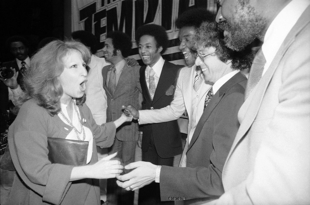 Singer Bette Midler, left, greets members of the soul group, the Temptations, and unidentified guests, are shown at the new in-spot disco, Studio 54, at a party given to announce the Temptations' new recording contract with Atlantic records in New York, May 9, 1977. (AP Photo/Richard Drew)