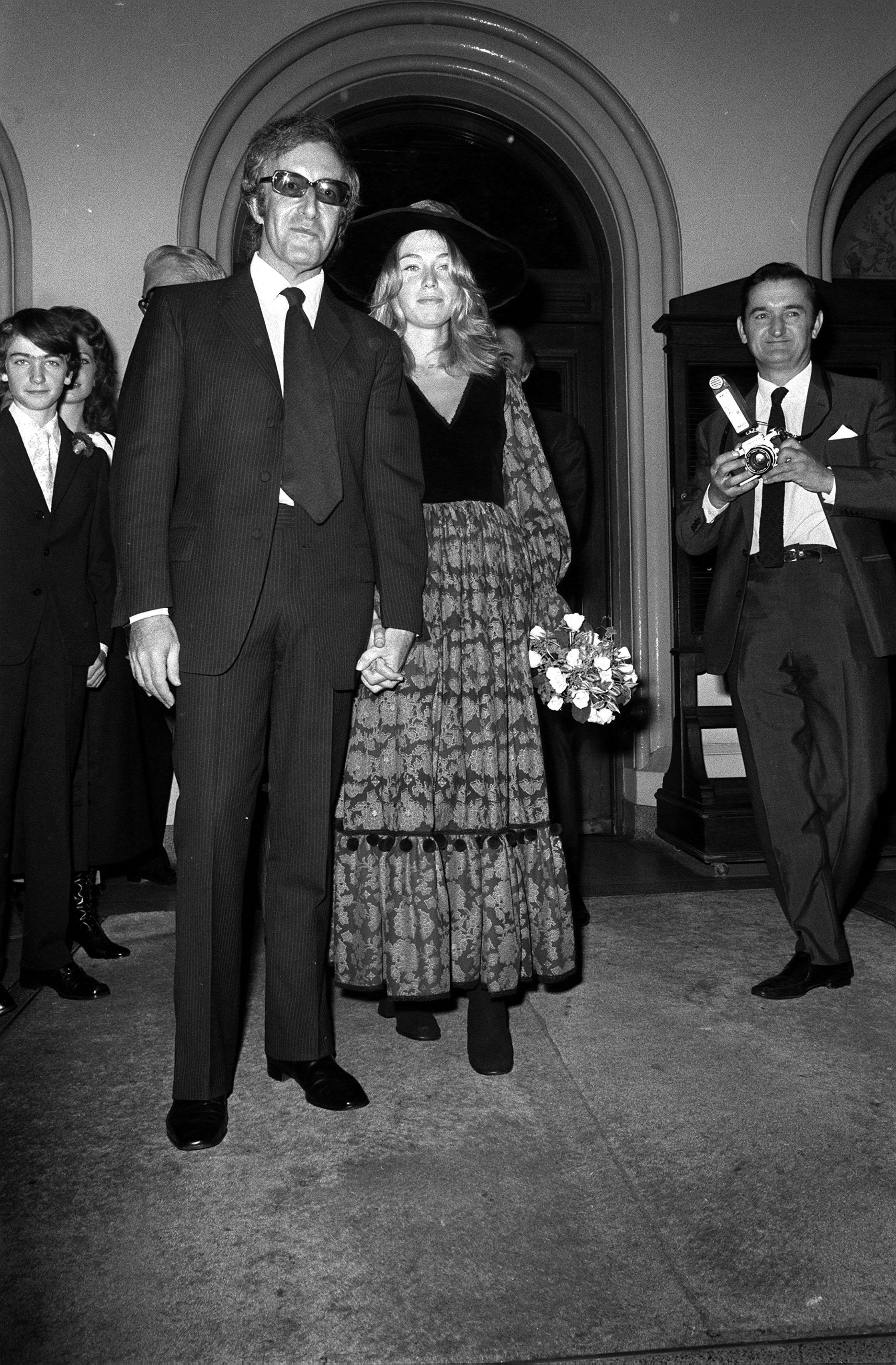 Peter Sellers, in conventional dark pin-stripped suit, and his bride, the former Miranda Quarry, in rich puce-coloured Gypsy-styled maxi dress, after their marriage at Caxton Hall Register Office. * The Bride is step daughter of Cunard deputy chairman Lord Mancroft. Her dogs were her bridesmaids and Sellers left her during the honeymoon. It was Sellers third marriage. His first, to Anne Howard, in 1951, was dissolved in 1964. He married actress Britt Eckland the same year.
