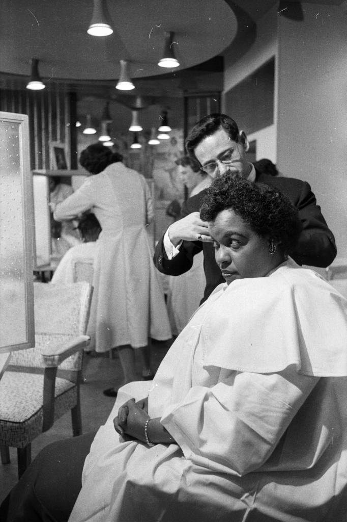 30th April 1957:  A customer has her hair straightened out at pianist Winifred Atwell's hairdressing salon in Brixton, London.  (Photo by Lee Tracey/BIPs/Getty Images)