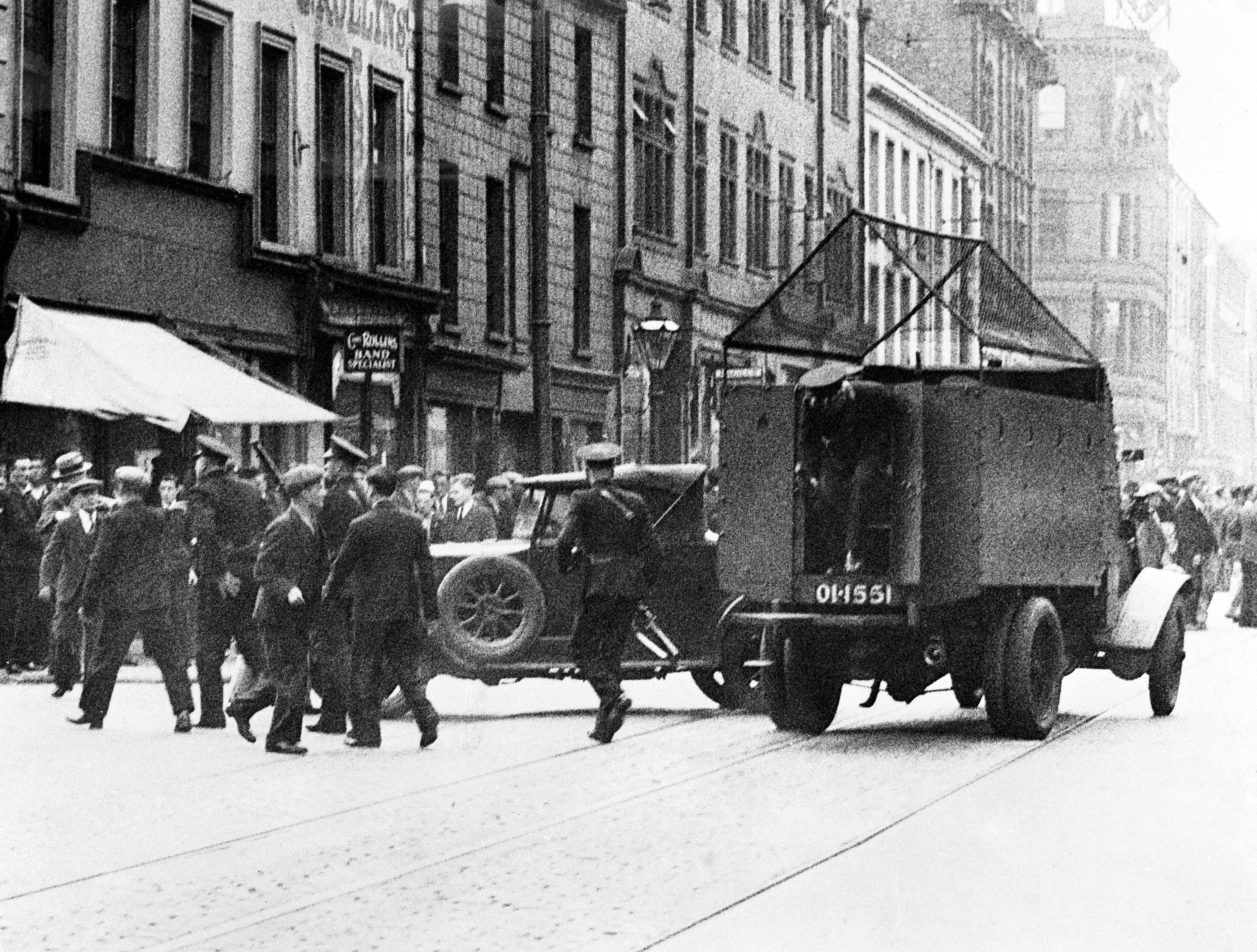Police armed with rifles descending from an armoured car to pursue gunmen in crowd following the shooting affray when James Lyttle's funeral procession passed York Street, Belfast on July 16, 1935. Cages for protection. (AP Photo/MAC)