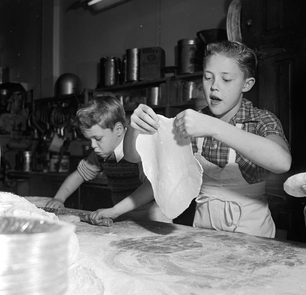circa 1955:  Young television stars Glenn (left) and Ronnie Walken, later film star Christopher Walken, roll out dough for pie crusts at their father's bakery.  (Photo by Orlando /Three Lions/Getty Images)