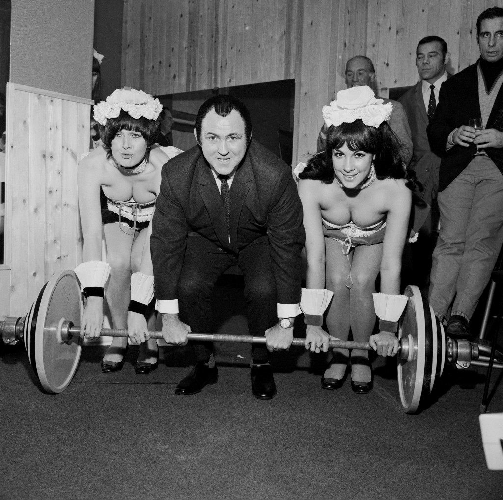 Wrestler Mick McManus (c) enlists two Penthouse Pets, Mary Crossley (l) and Hazel Perring (r), to help him lift a 276lb weight in Dave Prowse's exercise advice centre