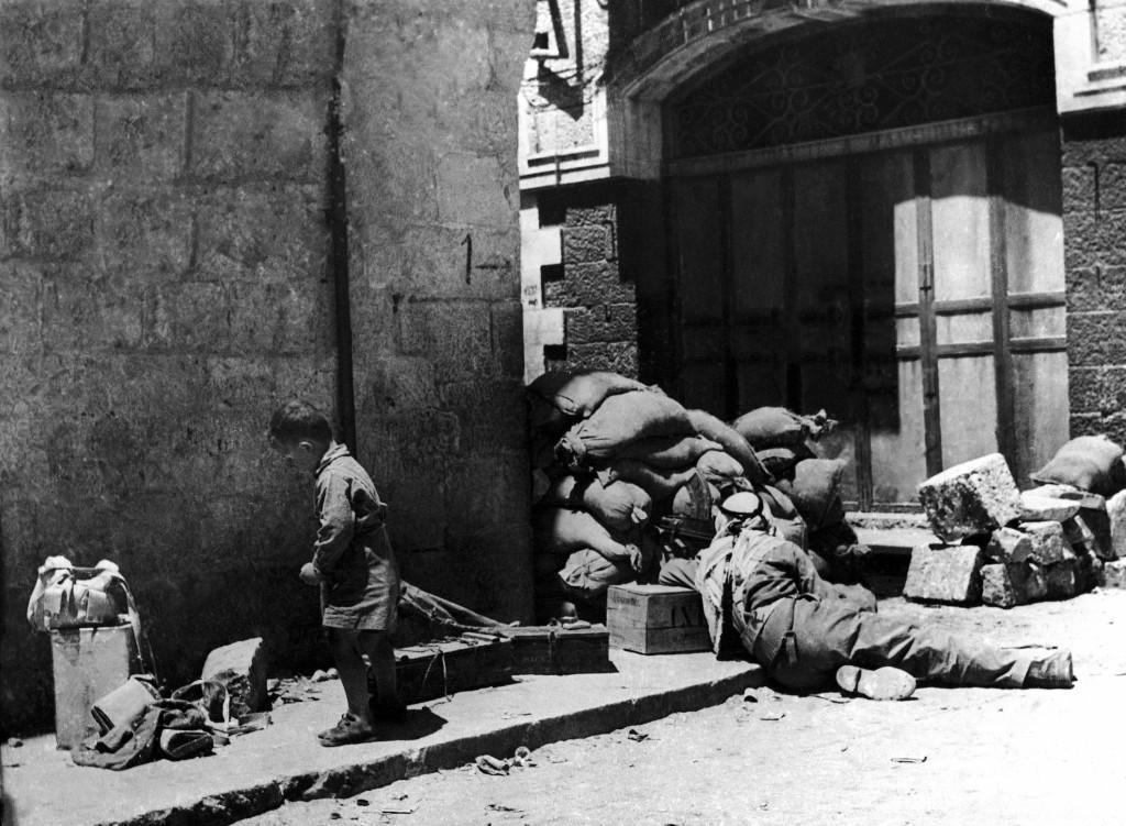 An Arab soldier manning a machine gun, takes cover behind sand bags on a street near the New Gate in the old city of Jerusalem, Palestine on May 29, 1948 during the Jewish Arab conflict while a little boy on the left, unimpressed by the deadly atmosphere plays in the debris covering the pavement. (AP Photo) Ref #: PA.10005843 Date: 29/05/1948