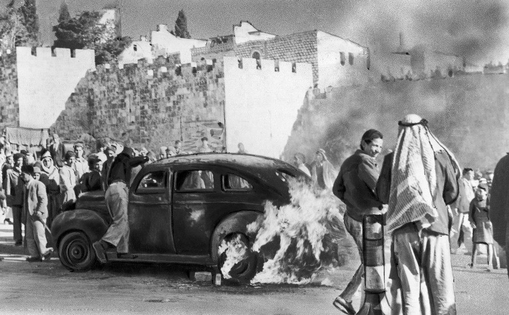 A Jewish cab is set ablaze by an angry mob near the Damascus Gate in Jerusalem, Israel on December 29, 1947 after Jews shooting from a taxi assassinated 15 persons, among them 12 Arabs, 2 British constables and a Jew. (AP Photo) Ref #: PA.10005928 Date: 29/12/1947