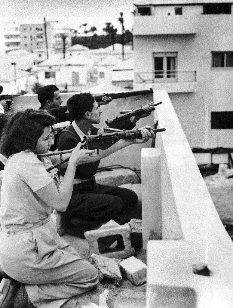 Members of the Jewish right-wing underground organization Irgun Zvai Leumi (National Military Organization in the Land of Israel) are armed with rifles, revolvers and automatic weapons as they take position on the rooftop of a Jewish house in case of Arab attack on the Jaffa - Tel Aviv border in the Manshiah Jewish quarter in Tel Aviv, Israel, on December 27, 1947. The Zionist guerrilla force began an armed revolt against British rule in Palestine. (AP Photo/James Pringle) Ref #: PA.10005962 Date: 27/12/1947