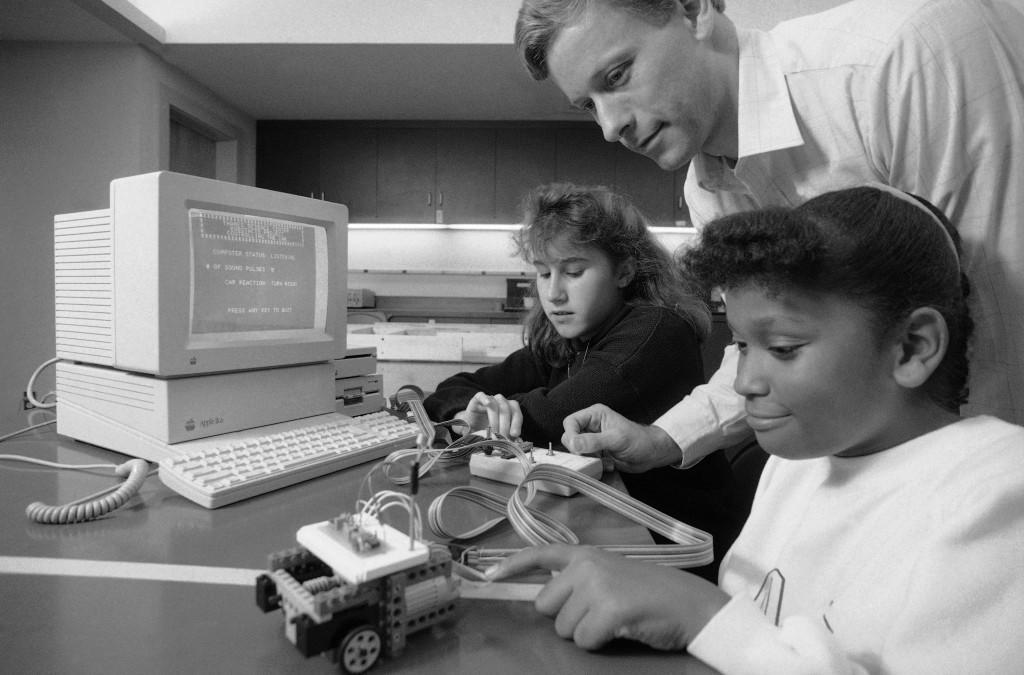 Crystal Robinson, 11, works with a small, kit-built robot, right, as Allie Chassanoff, 13, observes, left, with Rick Gaines, director of the Thames Science Center in New London, Connecticut on Dec. 4, 1989. Gaines conducts a robot building course, Project Robot Acts. The computer in the background helps run the robot. (AP Photo/Marty Reichenthal)
