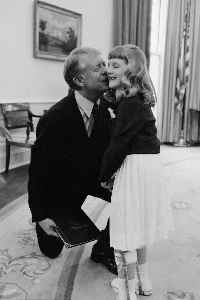 President Jimmy Carter kisses Claire Huckel, 7, of Philadelphia on the cheek during their meeting at the White House in Washington on Thursday, March 1, 1979. Claire is the 1979 National Easter Seal Child. (AP Photo/Ira Schwarz) Ref #: PA.10084782  Date: 01/03/1979