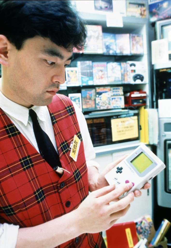 "An unidentified Tokyo salesperson plays with Nintendo's latest computer game, ""Game Boy, in Tokyo, Japan. Nintendo, which spent most of its one hundred year history producing playing cards, is leading the toy industry with computer games. Ref #: PA.10134336  Date: 01/01/1989"