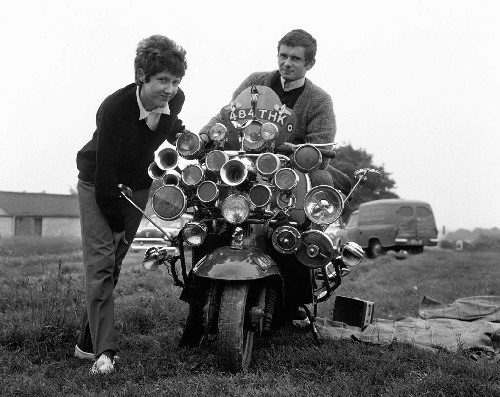 The modern fad for having as much sound and light as possible on your scooter reached the Epsom Downs for Derby Day. Proud owners are Roy Young and Linda Jarvis. Proud riders are Roy Young and Linda Jarvis at Derby Sunday on the Epsom Downs. Ref #: PA.1019137  Date: 31/05/1964