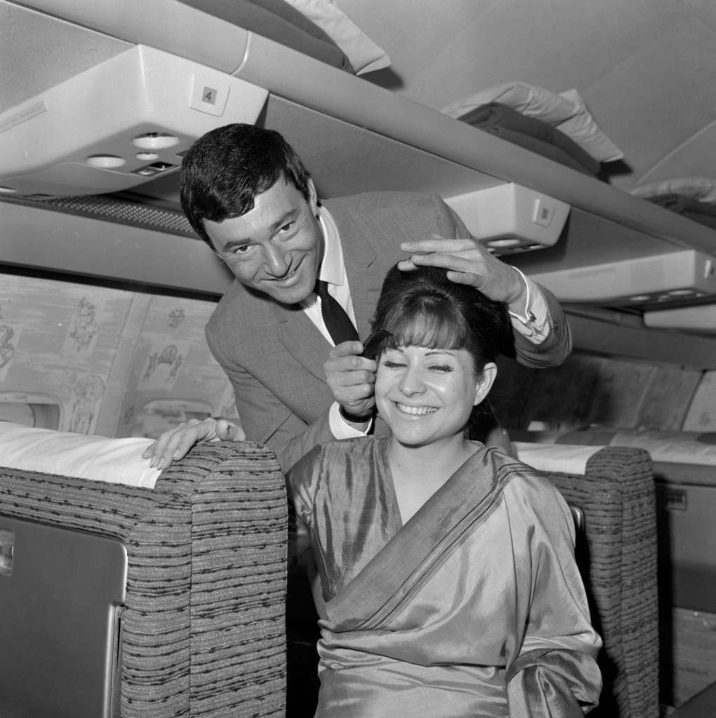 Hair stylist Vidal Sassoon, gives Air India hostess Ruby Bharucha a few hints on grooming hair at 40,000 feet, en route form London to New York where he is opening a salon. Archive-PA116756-1 Ref #: PA.10488497 Date: 27/05/1965