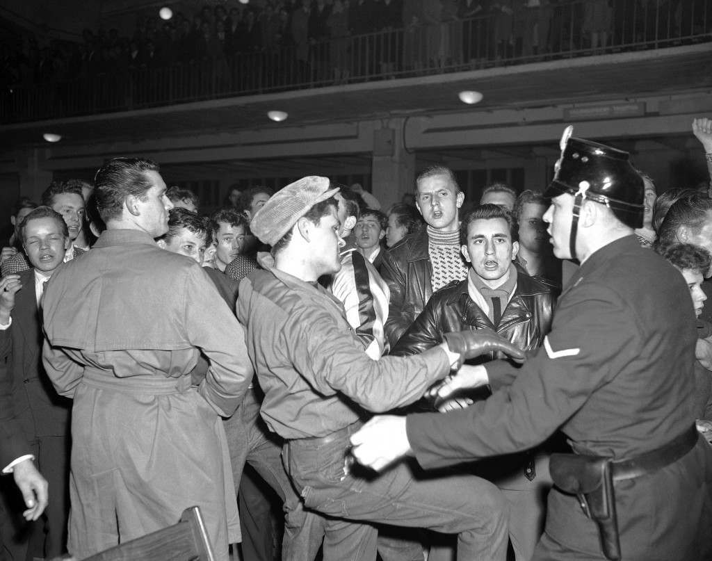 One of the seat-smashing youngsters who scared American rock 'n' roll singer Bill Haley off the stage during his performance in the Hamburg, West Germany, Ernst-Merck-Hall on Oct. 27, 1958. In a wild fist-and-stick battle numerous troublemakers were arrested by police when clearing the sold-out Ernst-Merck-Hall. Several policemen were injured. (AP Photo/Henry Brueggemann) Ref #: PA.10572634