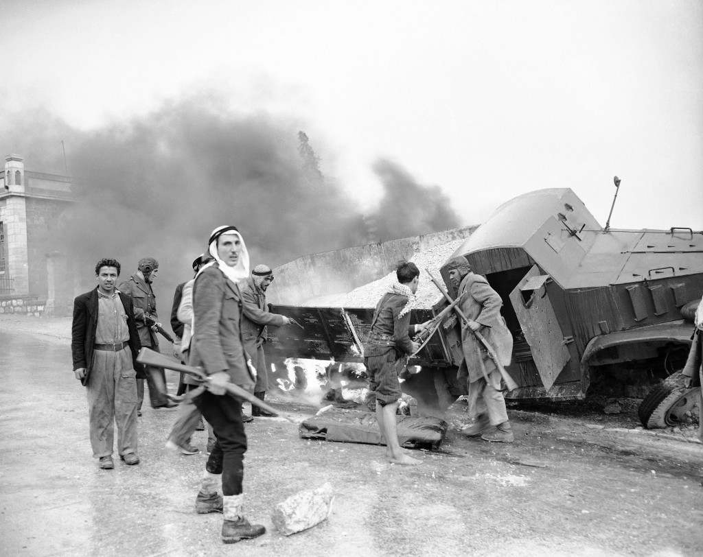 Arab snipers move away from a flaming Jewish truck in the Sheik Jarrah quarter of Jerusalem after dragging the body of driver from armored cab and dumping it on the road on March 7, 1948. The truck was caught in sniper fire, crashed into a wall and burst into flames. Ref #: PA.2539510 Date: 07/03/1948