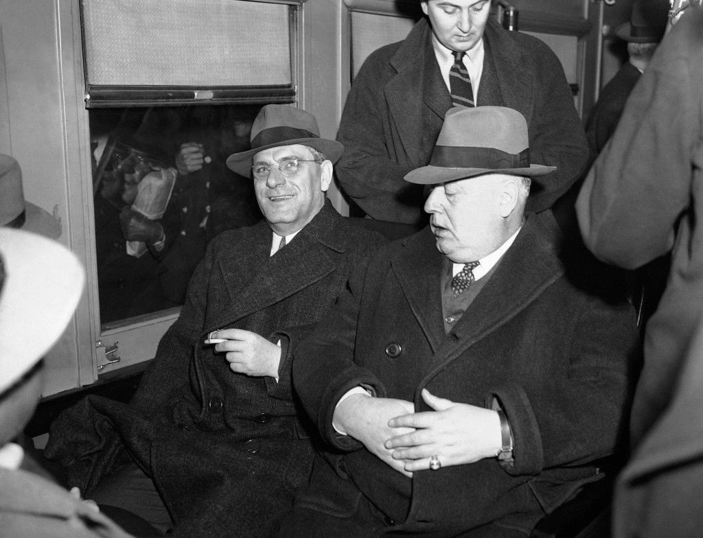 Fritz Kuhn, left, German American Bund leader, smiles as he boarded a train in New York en route to Sing Sing prison to serve a sentence of from two and a half to five years for theft of Bund funds. He's seated beside a detective in a railway car at Grand Central terminal in New York, Dec. 6, 1939. (AP Photo/Murray Becker) Ref #: PA.10716710  Date: 06/12/1939